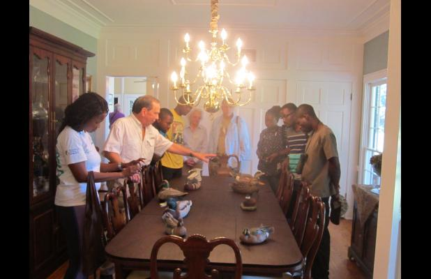 "Dr. L.J. Mayeux (left, pointing) explains the different types of ducks represented by his prized collection of hand-carved decoys to a group of Zambian wildlife officials who visited the parish recently. In addition to visiting Mayeux's ""Mallard Manor"" home, the group also toured Grand Cote National Wildlife Refuge, which is adjacent to Mayeux's home. {Photos by Raymond L. Daye}"